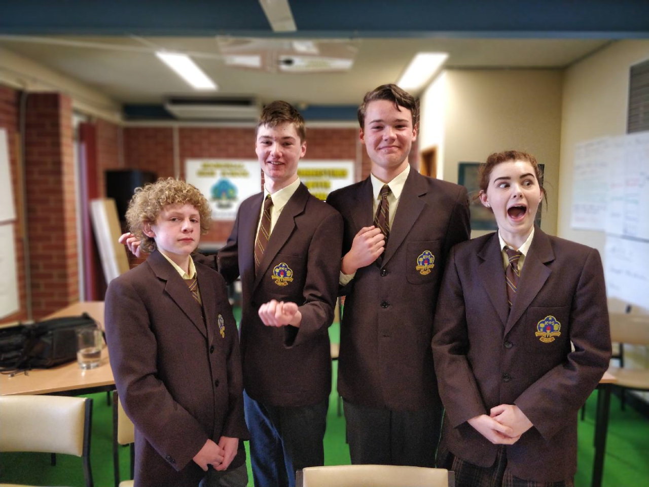 Four very happy students in school uniform in the library